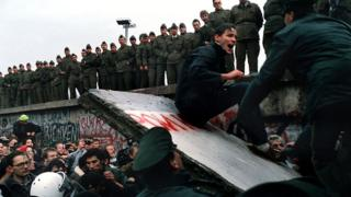 Next to a large crowd a man sits on a fallen piece of the Berlin Wall as border guards look on.