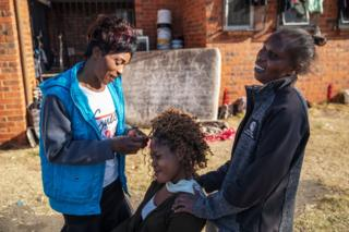 """A woman combs another outside the Tsolo Community Hall in Johannesburg""""s Katlehong township, on September 9, 2019, where around 250 people, mostly Zimbabwean and Malawian nationals, are hosted after being displaced due to a new wave of anti-foreigner violence that hit South Africa""""s financial capital."""