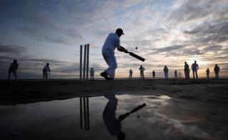 A player goes to hit a cricket ball as the sun goes down over the Solent.