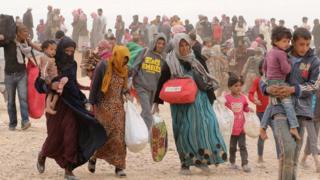 Syrian refugees wait to enter Jordan after fleeing the civil war