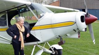 Mollie Anne Macartney stands next to a plane