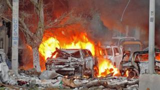 Wrecked cars burn at the scene of a terror attack in Mogadishu, June 2016