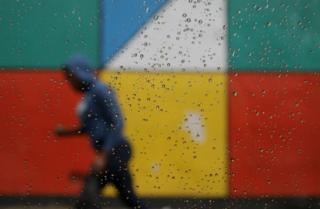 A blurred figure of a woman is pictured walking past a bright mural.
