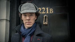 Benedict Cumberbatch dressed in a deerstalker outside 221B door.