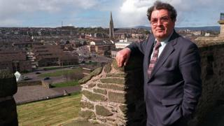 positive news John Hume, pictured on the walls of his home city Derry