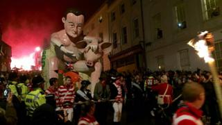 A crowd takes photos of the David Cameron effigy as it is paraded through Lewes