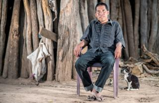 Chagabi Etacore sitting in a chair in the forest with a cat beside him