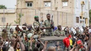 Armed members of the FAMA (Malian Armed Forces) are celebrated by the population as they parade at Independence Square in Bamako on August 18, 2020.