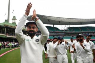 """India""""s captain Virat Kohli gestures to supporters as his teammates celebrate a 2-1 series victory over Australia following play being abandoned on day five in the fourth test match between Australia and India at the SCG in Sydney, Australia"""