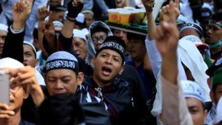 Demonstran memprotes pembakaran bendera Tauhid.
