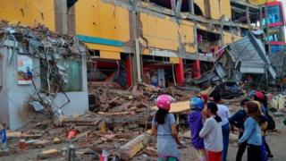 People stand in front of a damaged shopping mall in Palu
