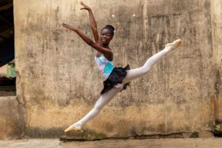 in_pictures A teenage girl performs a ballet jump outside the classroom.
