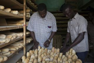 Mohammed Maiga (right) prepares loaves of bread to be placed on a delivery bike at Guemou Coura Bakery on 2 February 2019.