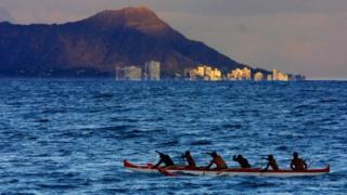 Des hommes rament leur canoe en direction de la plage de Waikiki à Honolulu (Hawaï). (Illustration)
