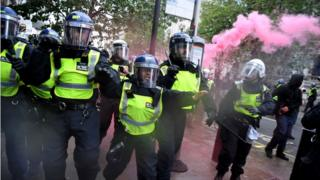 Police in riot gear clashed briefly with crowds in London