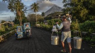 Жизнь неподалеку от вулкана может быть непредсказуемой. Люди, живущие близ вулкана Майон на Филиппинах, занимаются своими делами, несмотря на небольшое извержение