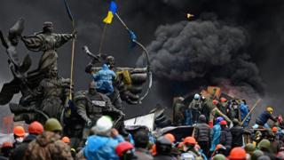 Протестувальники на тлі барикад і диму