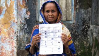A woman holds up a draft list of the National Citizen's Register in Assam