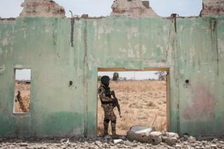 A soldier stands next to the ruins of Government Girls Secondary School Chibok in 2016.