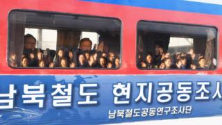Delegasi dari Korea Selatan melambaikan tangan dari selagi kereta yang mereka tumpangi membawa mereka ke Korea Utara (30 November 2018)