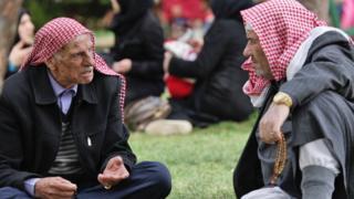 Men sit talking in a predominantly Syrian neighbourhood in Gaziantep