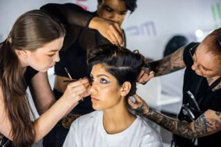 Hair and make-up artists work on a model backstage.