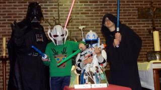 A man and three children dressed as Star Wars characters