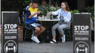 Young couple sitting at a restaurant in London at the start of the government's Eat Out to Help Out scheme