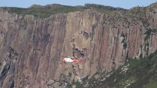 Irish Coastguard helicopter R118 hovering while rescuing two climbers at Fair Head in County Antrim