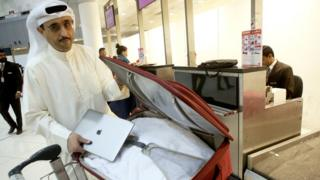 Kuwaiti social media activist Thamer al-Dakheel Bourashed puts his laptop inside his suitcase at Kuwait International Airport in Kuwait City before boarding a flight to the US