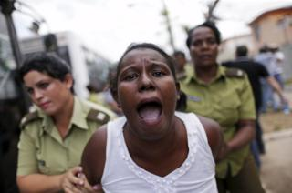 "A member of the ""Ladies in White"" dissident group shouts as she is led away by police officers in Havana"