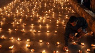 Pakistani people light candles to pray for the victims who were killed in an attack at the Army run school in Peshawar