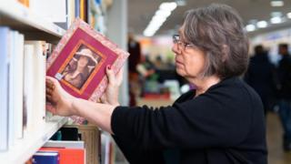Jacqui, volontaire d'Oxfam, met un livre sur une étagère dans la boutique de Wimbledon