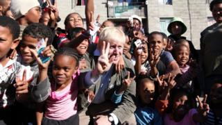 Boris Johnson pictured with a group of children giving a peace sign in Cape Town