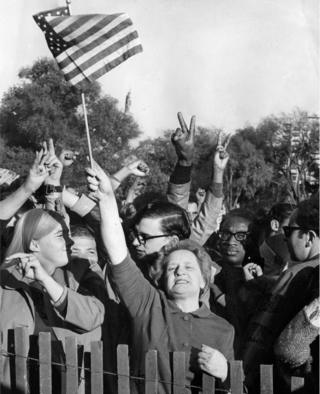 "Viola Woods, of Boston, waved an American flag and shouted, ""Hooray for President Nixon,"" amid the crowd on Moratorium Day rally crowd on Boston Common, Oct. 15, 1969"