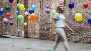 Balonlarla yürüyen kadın