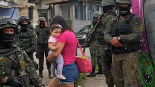 Mulher passa por soldados com crianças no colo