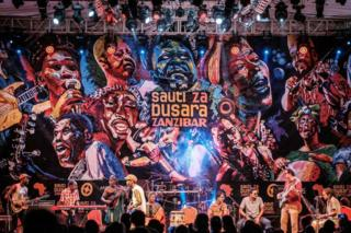 African musicians perform in front of a huge mural on stage at the 16th International African music festival 'Sauti za Busara' at the Old Fort in Stone town, Zanzibar, on 8 February 2019.