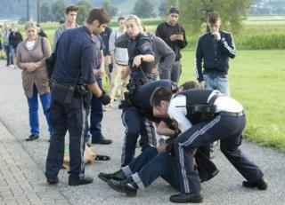 police officers arresting a man who is on the ground, 16 August 2016