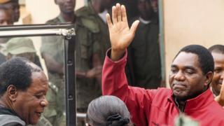 """Zambian opposition leader Hakainde Hichilema waves to supporters from a police van as he leaves a courtroom in Lusaka on April 18, 2017. Hichilema""""s arrest on treason charges - after his convoy allegedly refused to give way to the president""""s motorcade on a main road in the west of the country - has fanned political tensions in Zambia"""