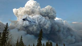 A helicopter flies past a wildfire in Fort McMurray, Alberta on Wednesday, May 4, 2016