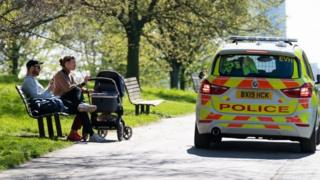 A police car near two people with a pram sat on a bench