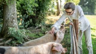 Princess Anne tends to pigs on her estate