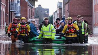 Mountain Rescue teams and soldiers help people to evacuate their homes in York as flood waters rise.