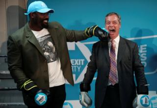 in_pictures Brexit Party leader Nigel Farage poses with boxer Dereck Chisora during a visit to a boxing gym in Ilford, Essex.