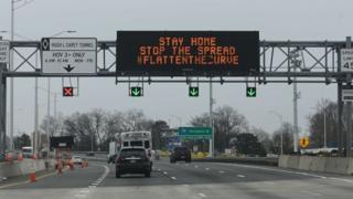 Cars drive under an electronic sign board warning drivers about coronavirus, COVID-19,on a highway near the Verrazano Bridge on March 30, 2020 in New York.