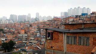 Casas em Paraisópolis, com prédios ao fundo