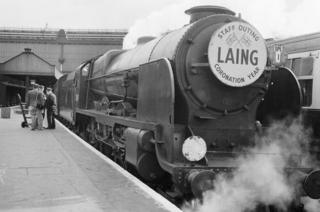 A train engine with a Laing sign on the front