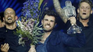 The Netherlands' Duncan Laurence holds up the eurovision glass microphone trophy