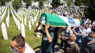 Men carry a coffin at a graveyard during a mass funeral in Potocari